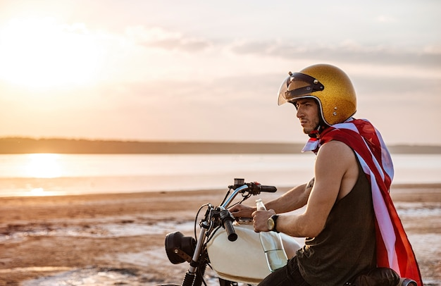 Giovane uomo brutale in casco d'oro e mantello bandiera americana seduto sulla sua moto