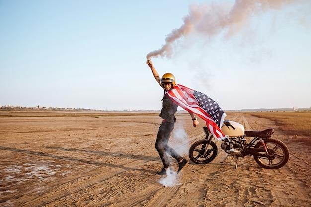 Giovane uomo brutale che indossa mantello bandiera americana e casco d'oro che tiene bomba fumogena nel deserto