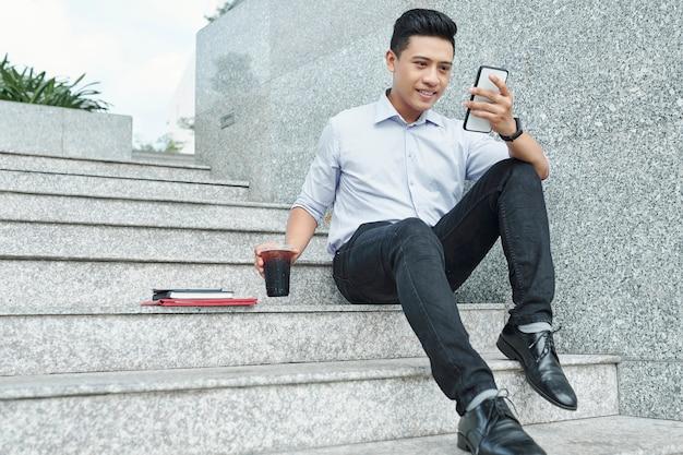 Giovane uomo d'affari che controlla telefono
