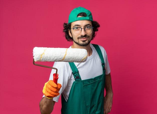 Giovane uomo costruttore che indossa un'uniforme con berretto e guanti che porge la spazzola a rullo