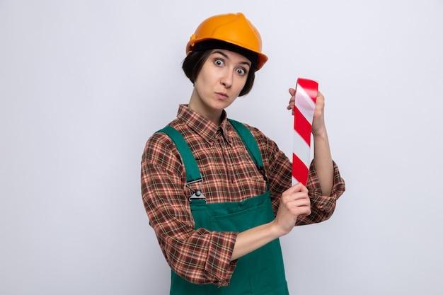 Giovane donna del costruttore in uniforme da costruzione e casco di sicurezza che tiene il nastro adesivo che sembra sorpresa