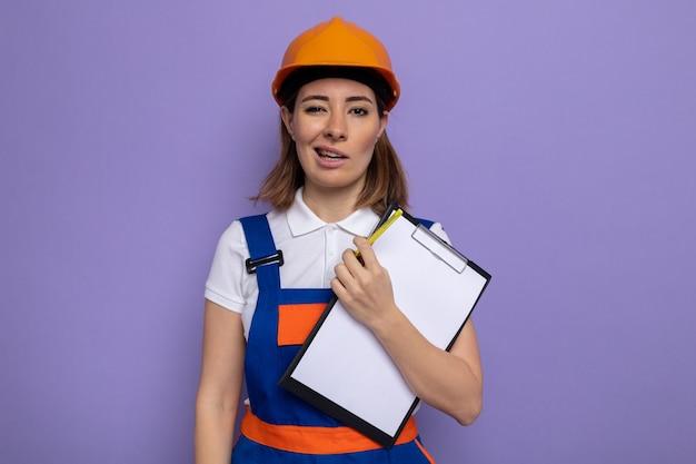 Giovane donna del costruttore in uniforme da costruzione e casco di sicurezza che tiene appunti con pagine bianche con sorriso scettico sul viso in piedi sopra il muro viola