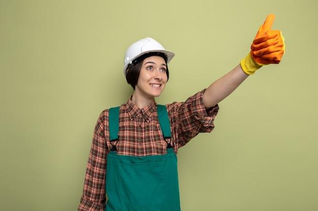 Giovane donna del costruttore in uniforme da costruzione e casco di sicurezza in guanti di gomma che guarda in alto sorridendo allegramente mostrando i pollici in piedi sul verde