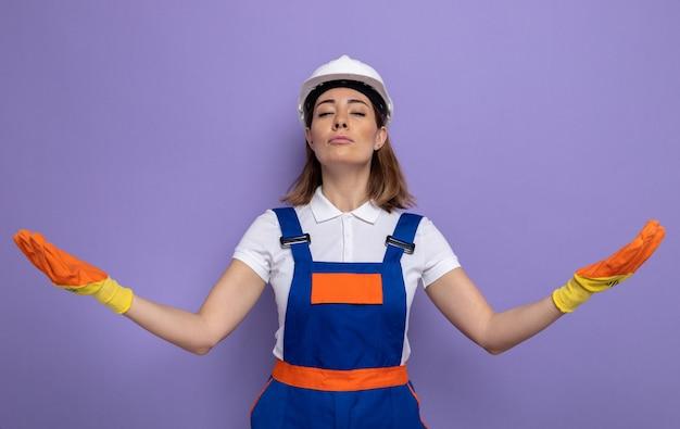 Giovane donna del costruttore in uniforme da costruzione e casco di sicurezza in guanti di gomma che sorride fiduciosa allargando le braccia ai lati in piedi sul viola