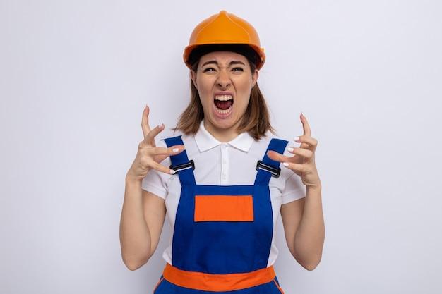 Giovane donna del costruttore in uniforme da costruzione e casco di sicurezza che grida e urla con le braccia alzate essendo frustrata e pazza pazza in piedi su bianco