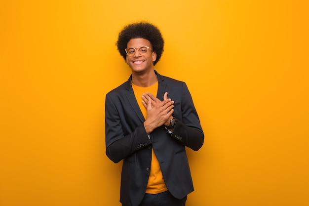 Uomo afroamericano di giovani affari su una parete arancione che fa un gesto romantico
