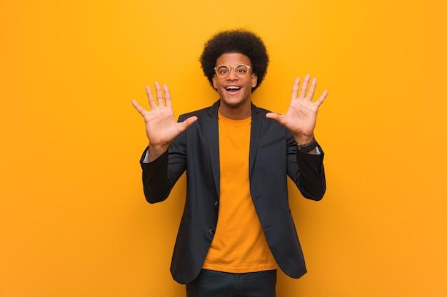 Giovane uomo afroamericano di affari sopra un muro arancione che mostra il numero dieci