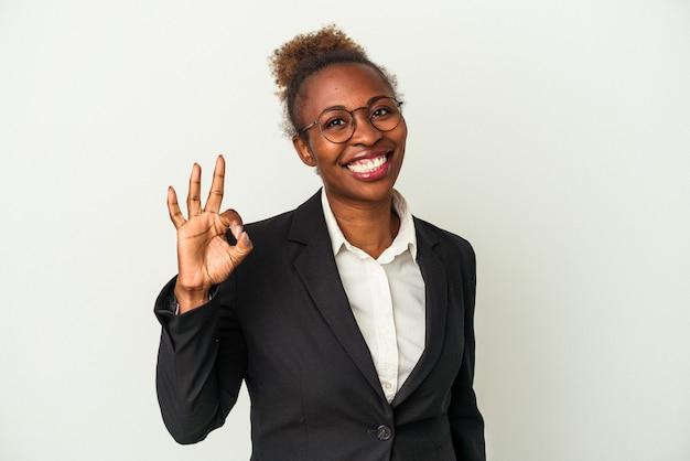 Giovane donna afroamericana di affari isolata su fondo bianco allegro e sicuro che mostra gesto giusto.