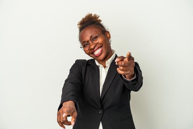 Giovane donna afroamericana di affari isolata sui sorrisi allegri del fondo bianco che indicano alla parte anteriore.