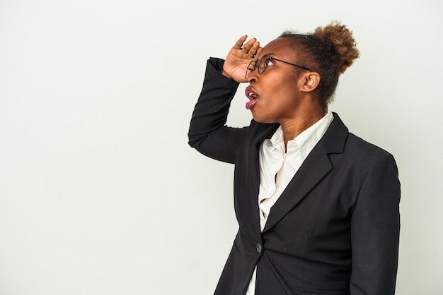 Giovane donna afroamericana di affari isolata su fondo bianco che guarda lontano tenendo la mano sulla fronte.
