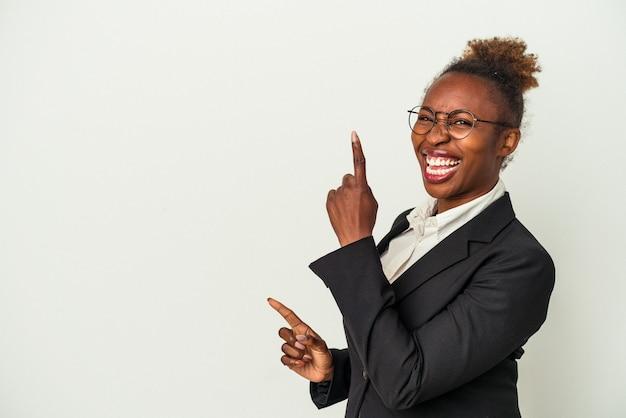 Giovane donna afroamericana di affari isolata su fondo bianco che indica con l'indice uno spazio della copia, esprimente eccitazione e desiderio.