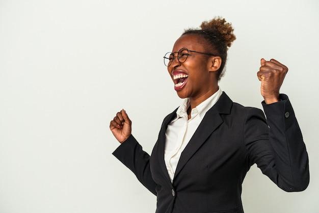 Giovane donna afroamericana di affari isolata su fondo bianco che alza il pugno dopo una vittoria, concetto del vincitore.