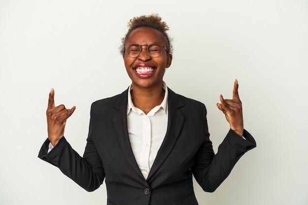 Giovane donna afroamericana di affari isolata su fondo bianco che mostra il gesto della roccia con le dita