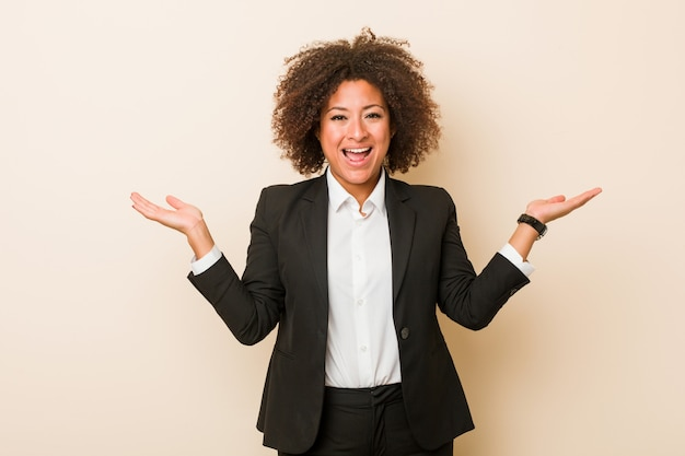 La giovane donna afroamericana di affari fa la scala con le armi, si sente felice e sicura.