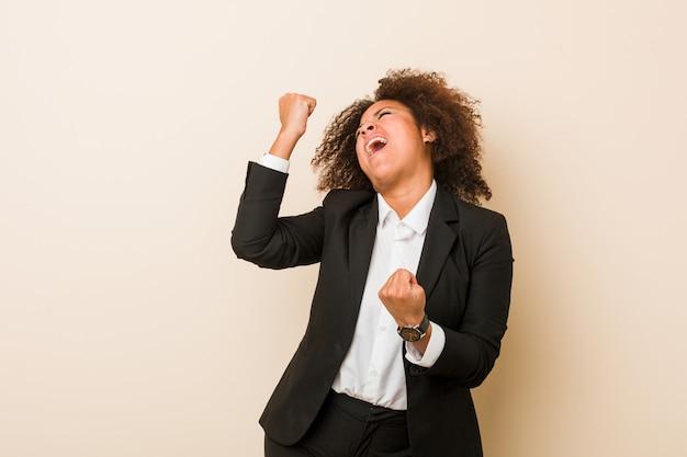 Donna afroamericana di giovani affari che alza pugno dopo una vittoria, concetto del vincitore.