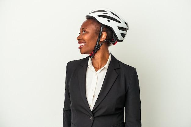 La giovane donna afroamericana di affari che indossa un casco della bici isolato su fondo bianco guarda da parte sorridente, allegra e piacevole.