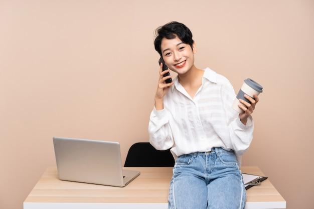 Ragazza asiatica di giovani affari nel suo caffè della tenuta del posto di lavoro da prendere