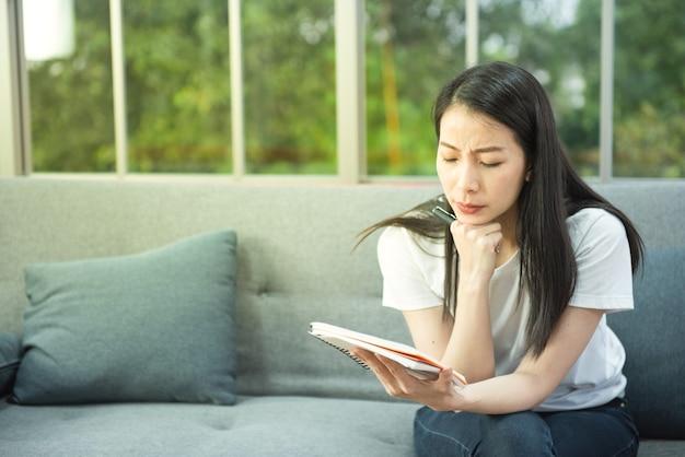 Giovane donna asiatica di affari distratta dal lavoro e pensando a qualcosa sul divano con il taccuino