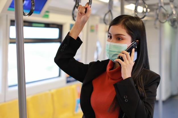Giovane donna asiatica di affari che indossa la protezione della maschera per prevenire l'infezione da virus covid19 da persone in treno, utilizzando la comunicazione dello smartphone in treno