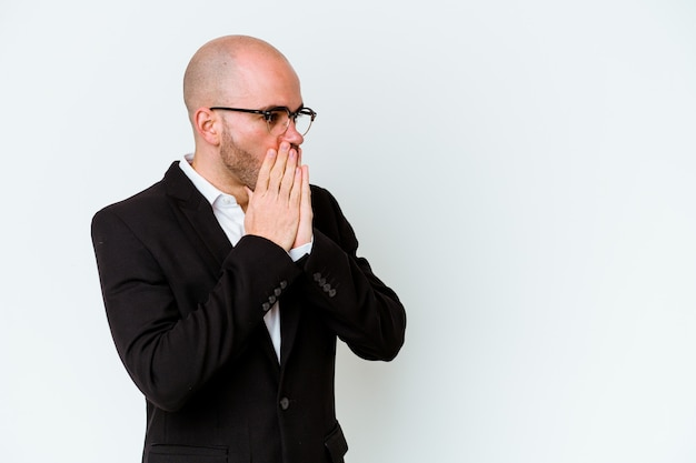 Giovane uomo calvo di affari isolato sulla parete blu premuroso che osserva ad uno spazio della copia che copre la bocca con la mano