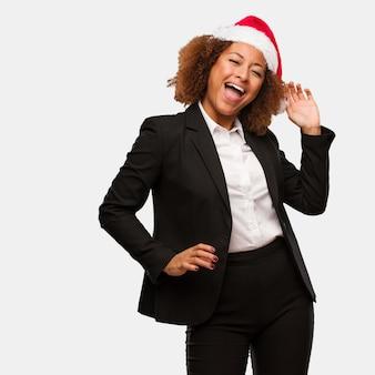 Giovane donna nera di affari che indossa un cappello di babbo natale di chirstmas che balla e che si diverte