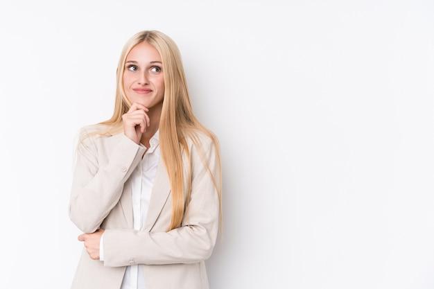 Giovane donna bionda di affari su bianco che osserva obliquamente con espressione dubbiosa e scettica.