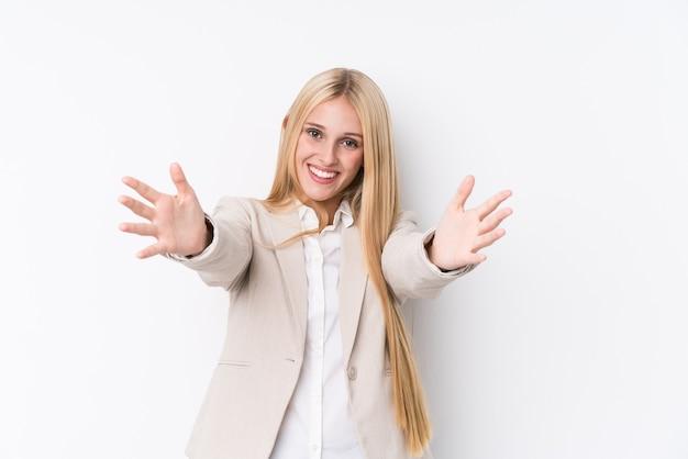 La giovane donna bionda di affari sulla parete bianca si sente sicura di dare un abbraccio alla telecamera.