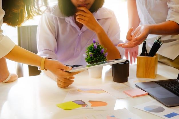Giovani imprenditori di brainstorming in ufficio incontro moderno con luce del mattino e tono vintage.