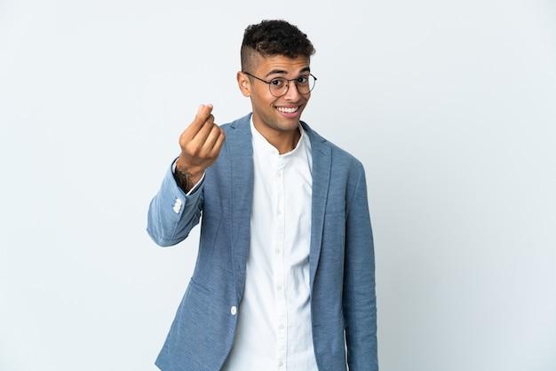 Giovane uomo brasiliano di affari su priorità bassa bianca che fa gesto di soldi