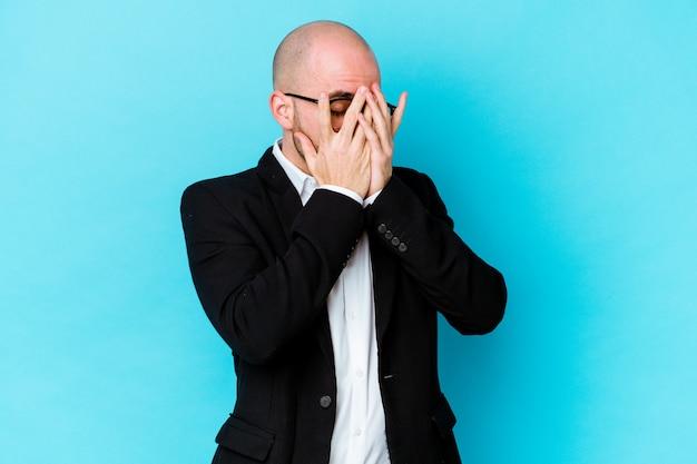 Giovane uomo calvo caucasico di affari isolato su sfondo blu lampeggia verso la telecamera attraverso le dita, imbarazzato che copre il viso.