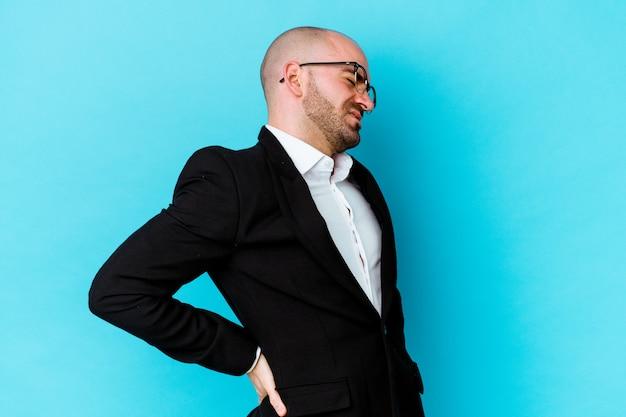 Giovane uomo d'affari caucasico calvo isolato su sfondo blu che soffre di mal di schiena.