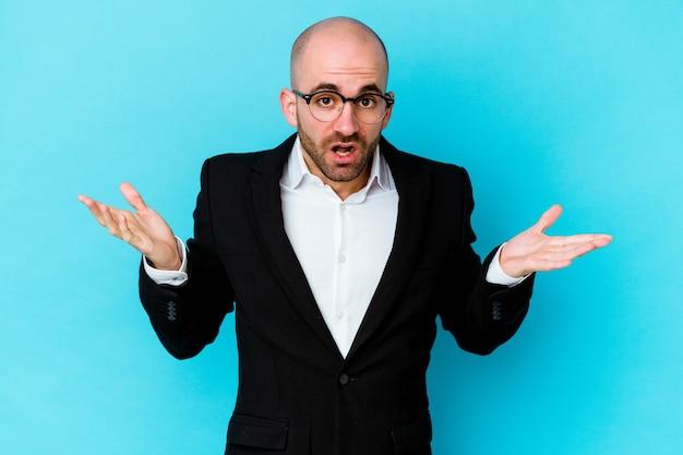 Uomo calvo caucasico di giovani affari isolato sulla parete blu che punta a diversi spazi di copia, scegliendo uno di loro, mostrando con il dito.