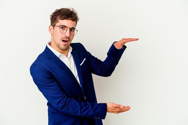 Uomo caucasico di giovani affari isolato su sfondo bianco scioccato e stupito in possesso di uno spazio di copia tra le mani.