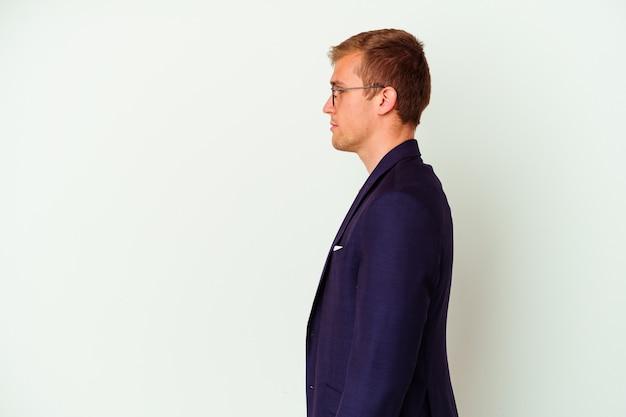 Uomo caucasico di giovani affari isolato su bianco che guarda a sinistra, posa laterale.