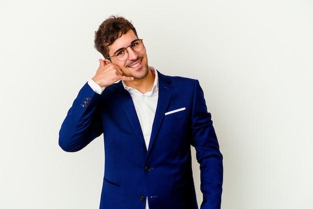 Uomo caucasico di giovani affari isolato sulla parete bianca che mostra un gesto di chiamata di telefono cellulare con le dita.