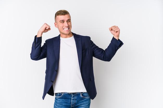Uomo caucasico di giovani affari che alza pugno dopo una vittoria, concetto del vincitore.