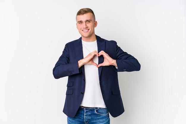 Uomo caucasico di giovani affari che sorride e che mostra una forma del cuore con le mani.