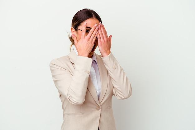 La giovane donna caucasica di affari isolata su fondo bianco sbatte le palpebre attraverso le dita spaventata e nervosa.