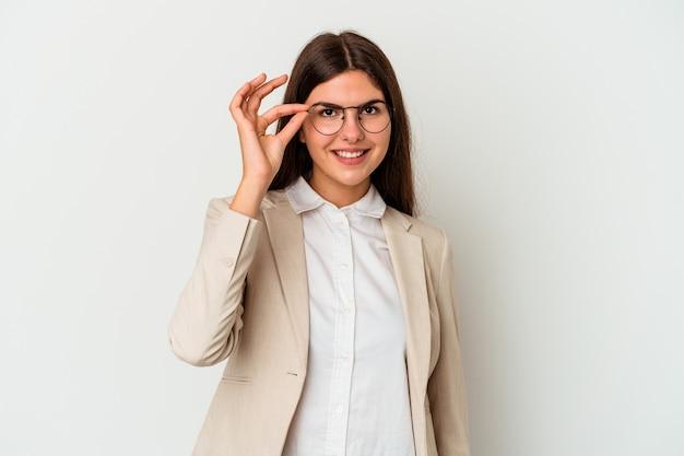 Giovane donna caucasica di affari isolata su fondo bianco eccitato mantenendo il gesto giusto sull'occhio.
