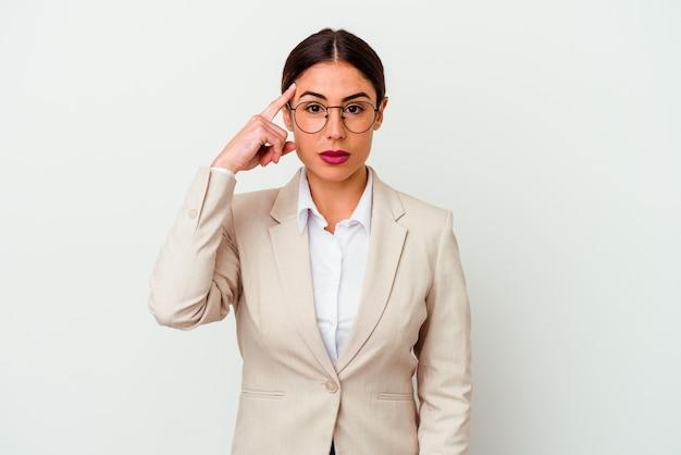 Young business woman indoeuropea isolata su sfondo bianco che punta il tempio con il dito, pensando, concentrato su un compito.