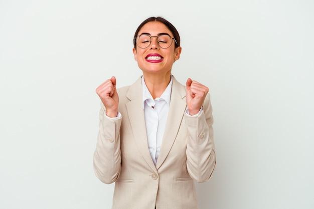 Giovane donna caucasica di affari isolata su priorità bassa bianca che alza il pugno, sentendosi felice e riuscito. concetto di vittoria.