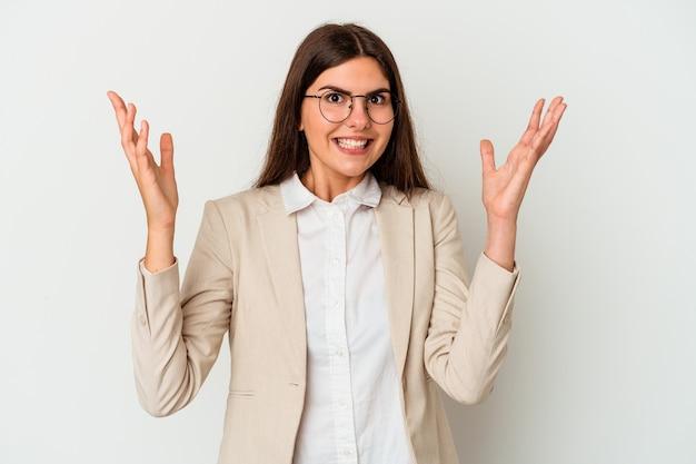Giovane donna caucasica di affari isolata su fondo bianco che riceve una sorpresa piacevole, eccitata e alzando le mani.