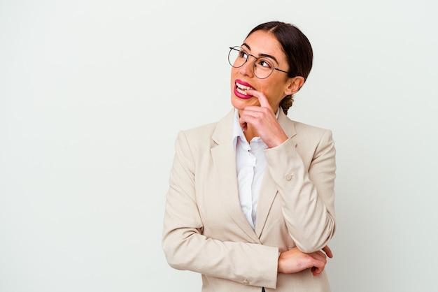 Giovane donna caucasica di affari isolata su priorità bassa bianca rilassata pensando a qualcosa guardando uno spazio di copia.