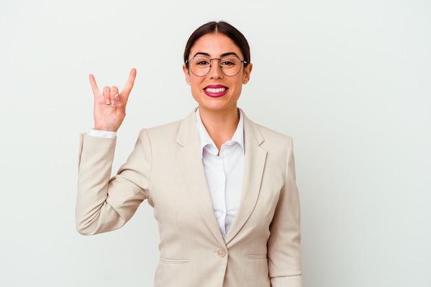 Giovane donna caucasica di affari isolata su priorità bassa bianca che mostra un gesto di corna come un concetto di rivoluzione.