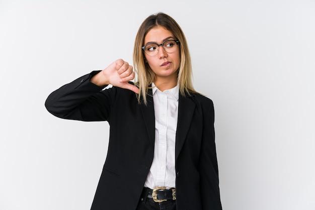 Giovane donna caucasica di affari che mostra un gesto di avversione, pollice in giù. concetto di disaccordo.