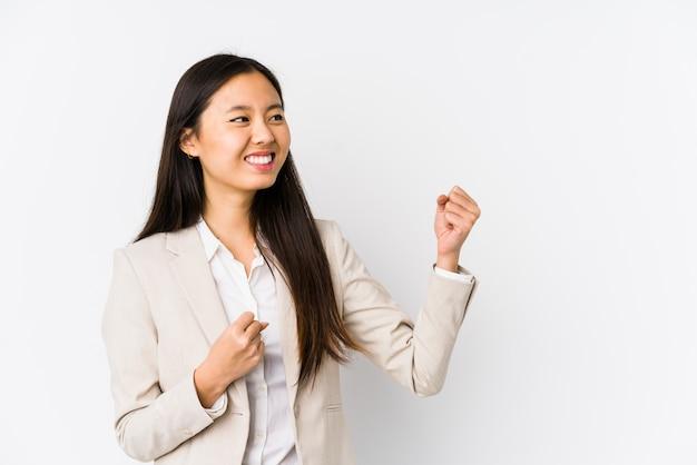 Pugno d'innalzamento isolato donna cinese giovane di affari dopo una vittoria, concetto del vincitore.