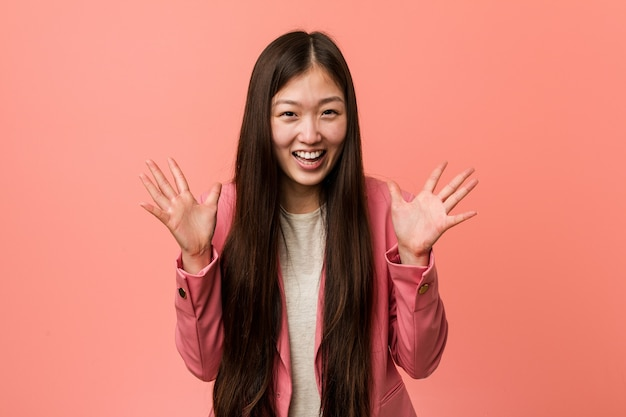 Giovane donna cinese di affari che porta vestito rosa che celebra una vittoria o un successo