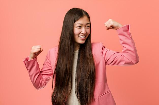 Donna cinese di giovani affari che indossa vestito rosa che alza pugno dopo una vittoria, concetto del vincitore.