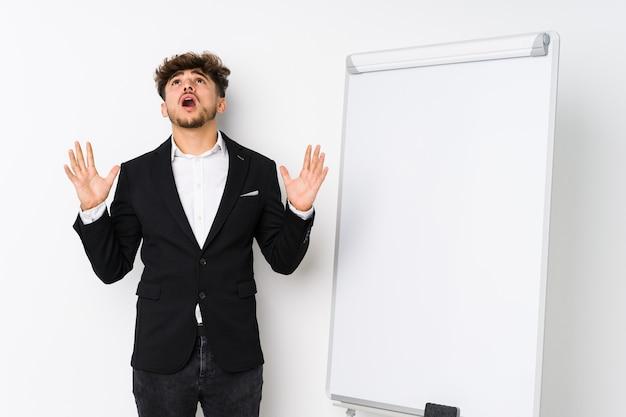 Young business coaching uomo arabo che grida al cielo, alzando lo sguardo, frustrato.