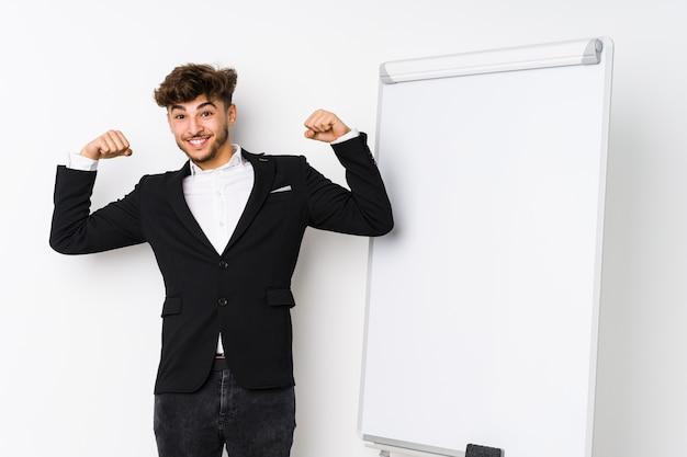 Young business coaching uomo arabo che mostra il gesto di forza con le braccia, simbolo del potere femminile